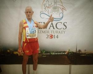 Emilio con sus medallas con el cartel del campeonato